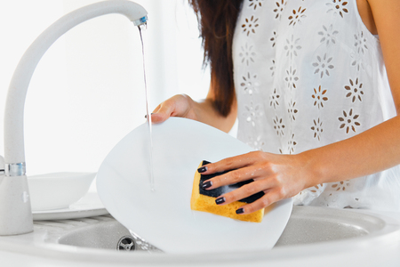 46115785 - young woman hands with nice manicure washing dishes in the sink in the kitchen using sponge with soap foam. close up view.
